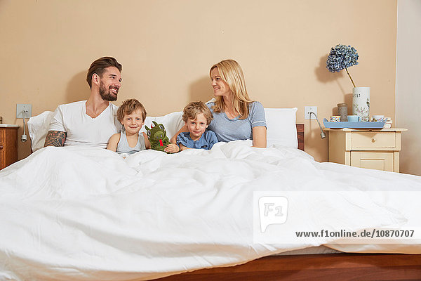 Mother and father in bed with sons and toy dragon