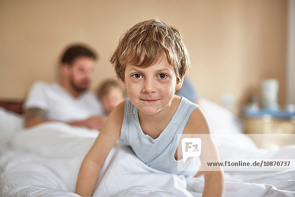 Boy on parents bed looking at camera smiling