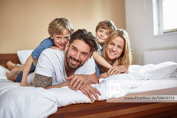 Boys on bed lying on top of parents looking at camera smiling