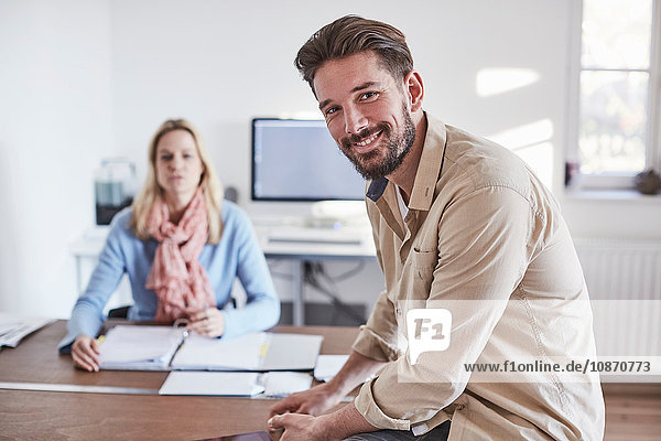 Man sitting on desk in office looking at camera smiling