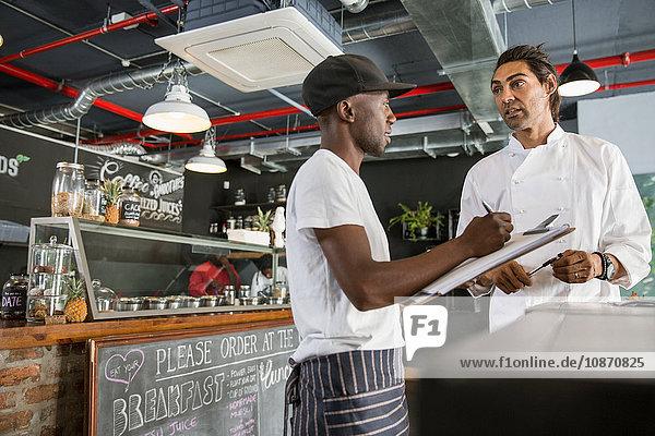 Angestellter im Restaurant im Gespräch mit dem Koch  Notizen in der Zwischenablage