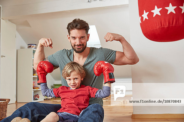 Boy wearing boxing with father  flexing muscles looking at camera