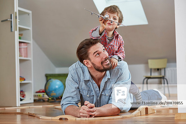 Father and son playing with toy aeroplane