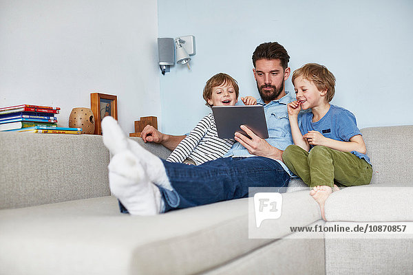 Father and sons on sofa using digital tablet
