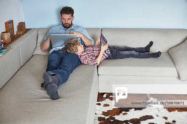 Boy lying on sofa with father using technology