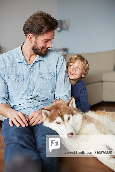 Father and son sitting with dog face to face smiling