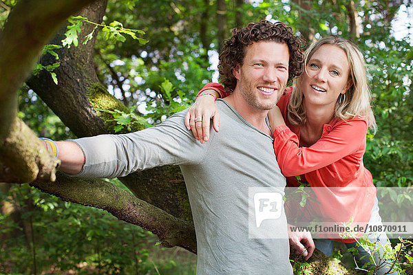 Couple leaning against tree looking at camera smiling