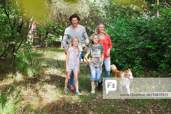 Familie mit Hund beim gemeinsamen Waldspaziergang