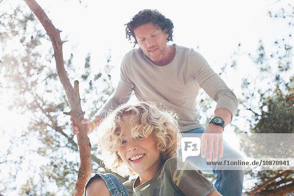 Vater und Sohn klettern auf Baum