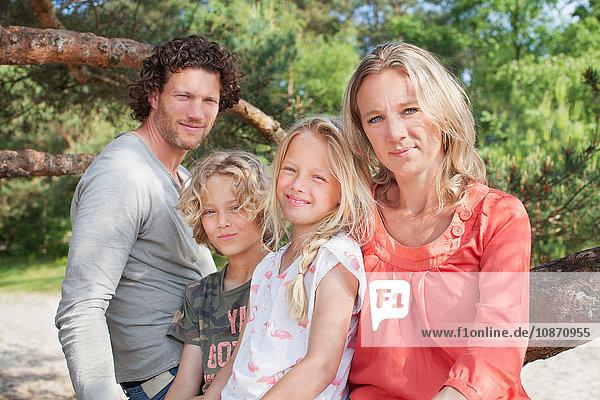 Familie sitzt zusammen und schaut lächelnd in die Kamera