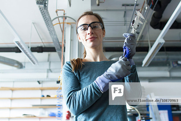 Low angle view of woman in workshop wearing safety goggles holding tool