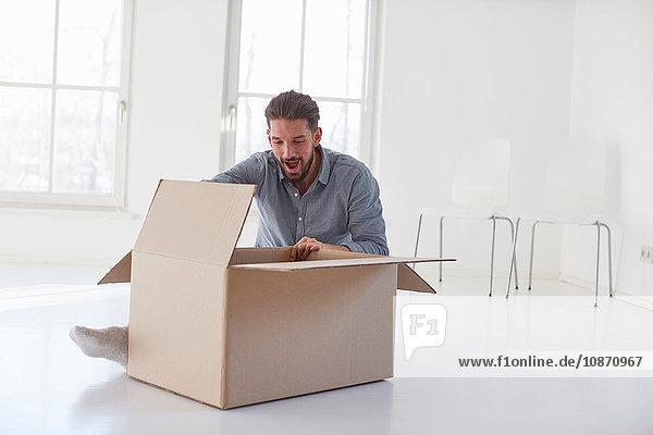 Junger Mann sitzt auf dem Boden und öffnet einen Karton im neuen Haus
