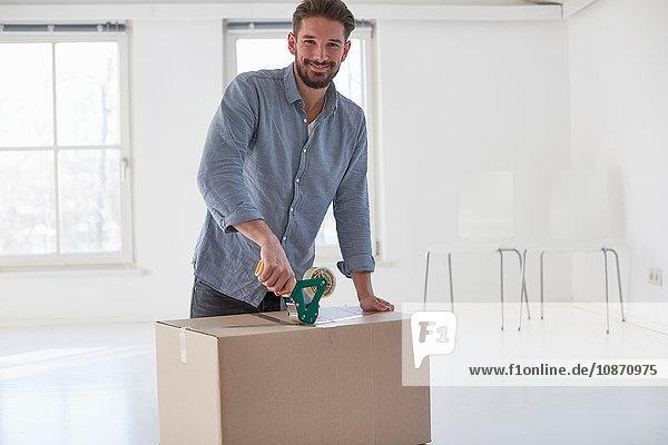 Porträt eines jungen Mannes  der bei einem Umzug einen Pappkarton zuklebt