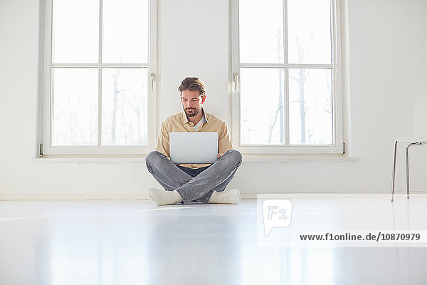 Young man sitting on floor browsing laptop in empty new home