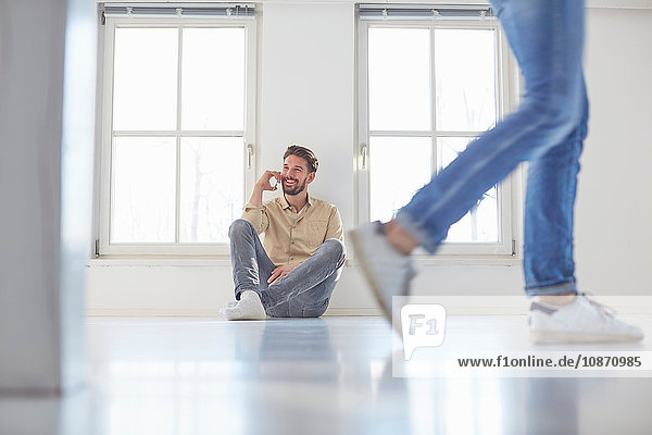 Man sitting on floor talking on smartphone in new home