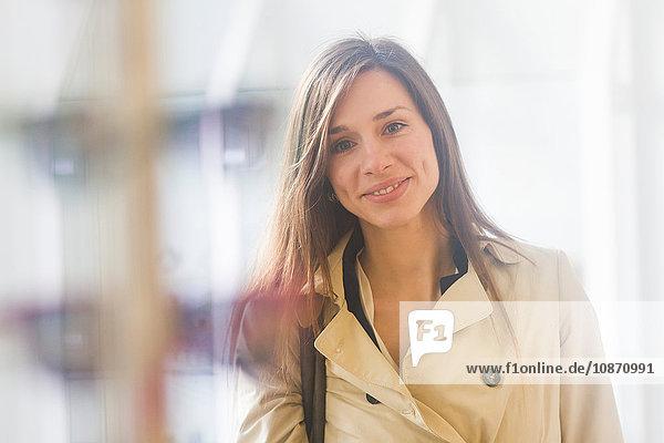 Woman wearing raincoat looking at camera smiling