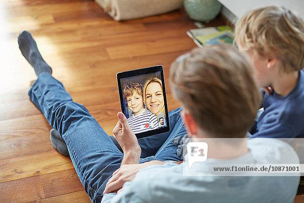 Mann und Sohn sitzen auf dem Boden und unterhalten sich mit Mutter und Bruder über ein digitales Tablet-Videogespräch