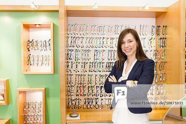 Woman in front of eye glasses display cabinet arms crossed looking at camera smiling
