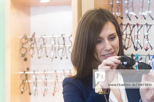 Frau im Geschäft schaut lächelnd auf Sonnenbrille