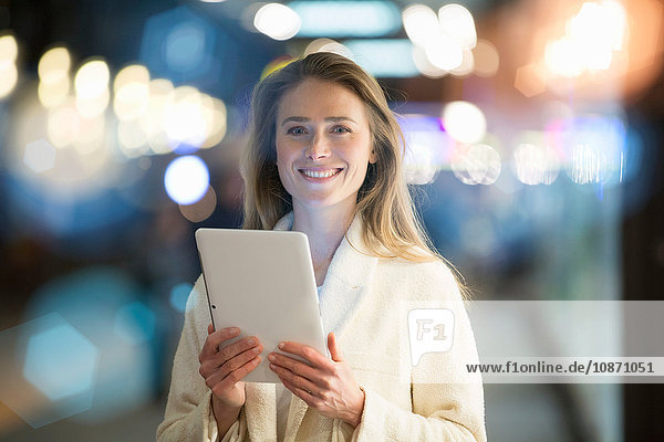 Portrait of businesswoman using digital tablet on city street at night