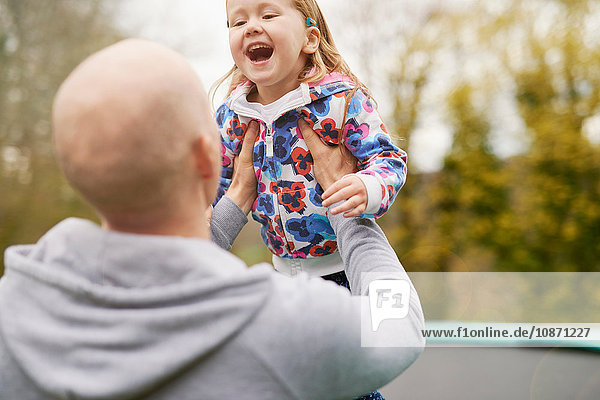 Father and daughter playing on trampoline