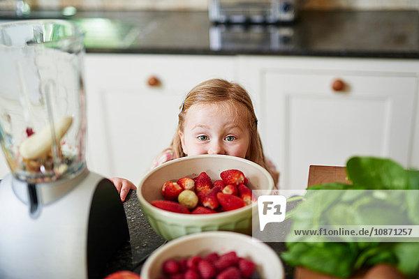 Mädchen  das über die Erdbeerschalen der Küchentheke schaut