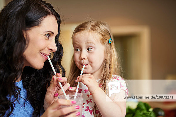 Mother and daughter face to face drinking smoothie with straws