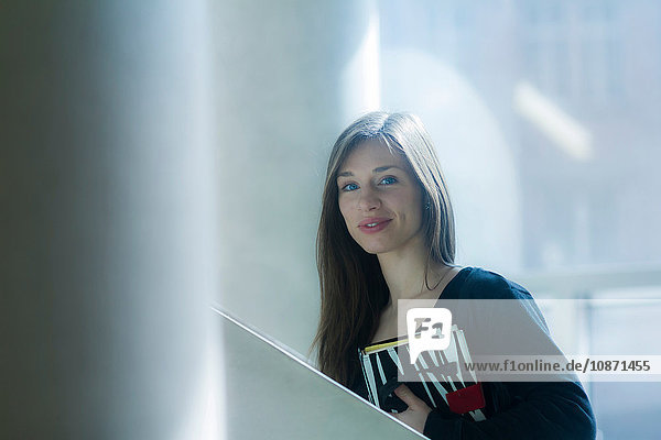Woman carrying notebook looking at camera smiling