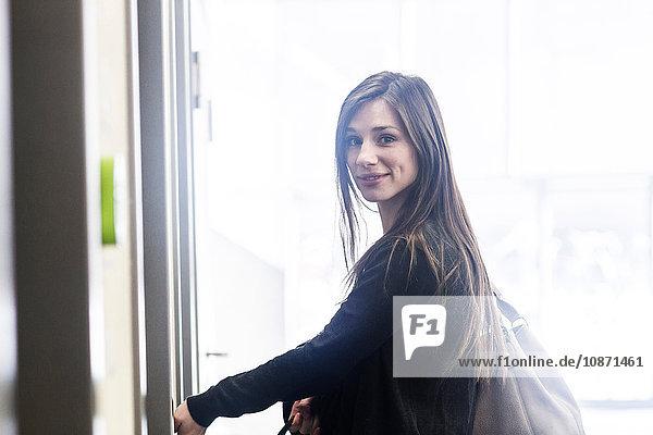Woman carrying handbag looking over shoulder at camera smiling