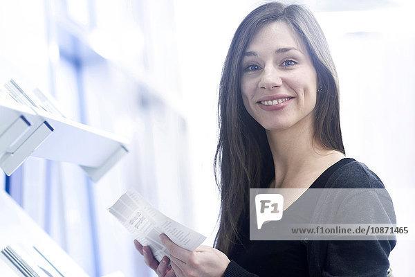 Woman holding paperwork looking at camera smiling