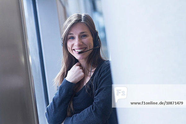 Woman wearing telephone headset looking at camera smiling