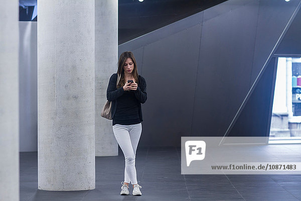 Full length front view of woman standing texting on smartphone