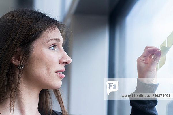 Side view of woman looking at adhesive notes stuck on window