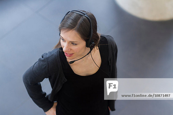 High angle view of woman wearing telephone headset looking away