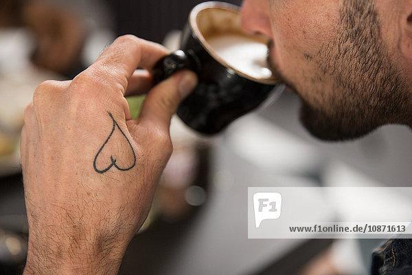 Ausschnitt eines tätowierten Mannes beim Kaffeetrinken