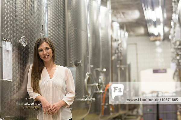 Portrait of young woman  leaning against fermentation tank in wine cellar