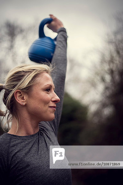 Low angle view of woman holding kettle bell  arm raised looking away
