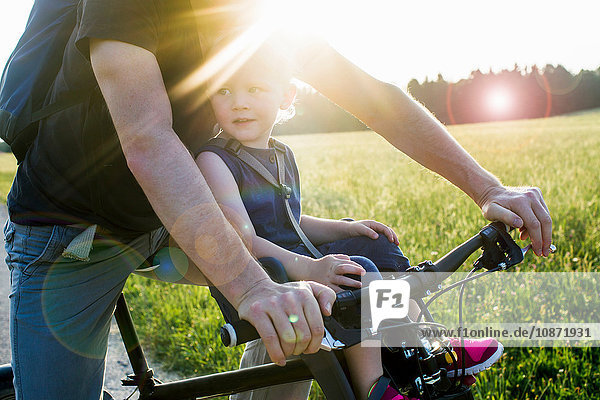 Father and baby daughter riding bike together  mid section