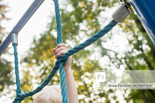 Baby girl on climbing frame at park  focus on hand