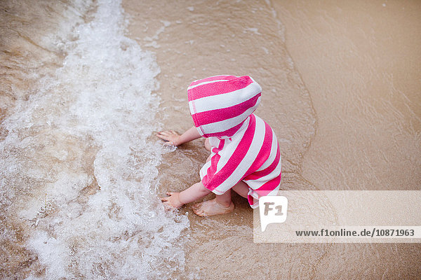 Baby girl sitting in the sea  rear view