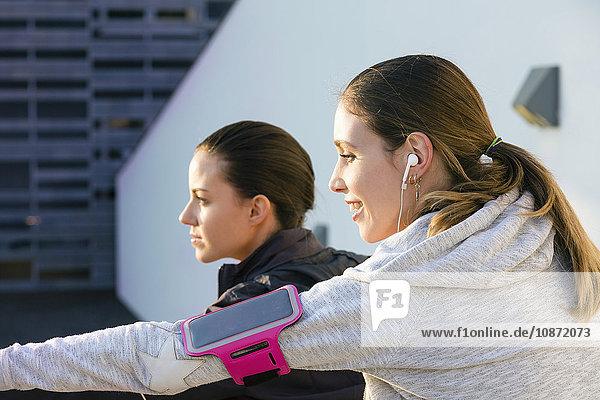 Junge Frau im Freien  trägt Kopfhörer und mp3-Player am Arm