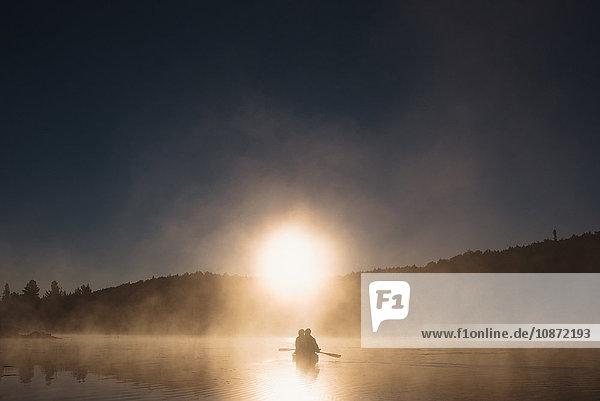 Älteres Ehepaar paddelt bei Sonnenuntergang auf dem See