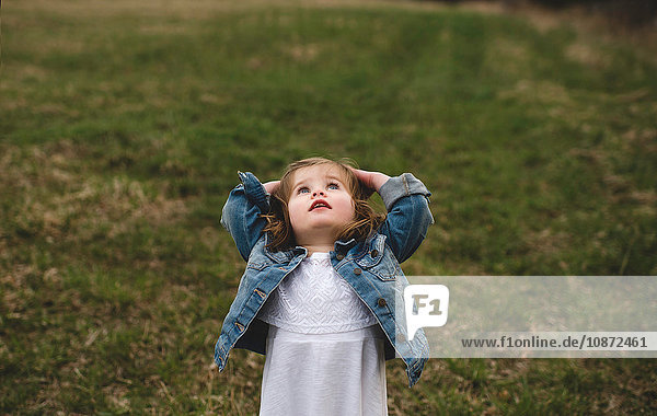 Young girl  in meadow  hands on head looking up into the sky