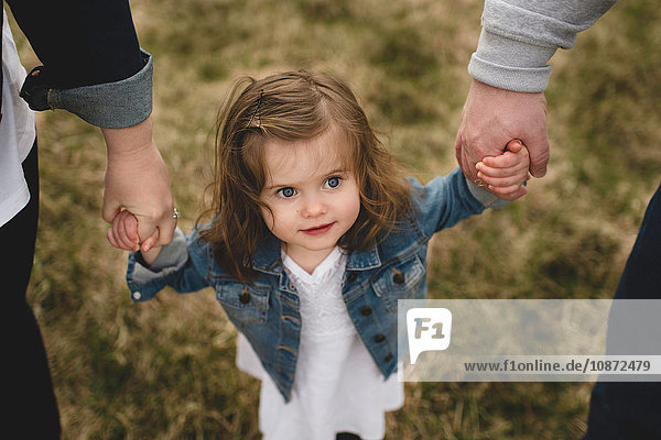 Mother and father holding young daughter's hands  outdoors  elevated view