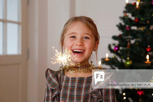 Mädchen vor dem Weihnachtsbaum mit Wunderkerze in der Hand und lächelndem Blick in die Kamera