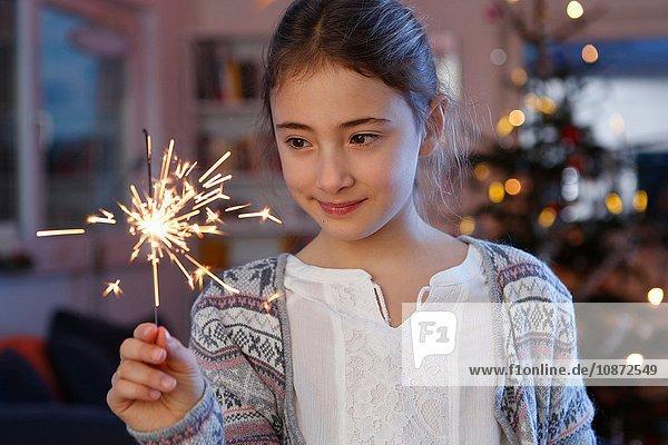 Mädchen vor dem Weihnachtsbaum mit einer Wunderkerze in der Hand schauen lächelnd nach unten