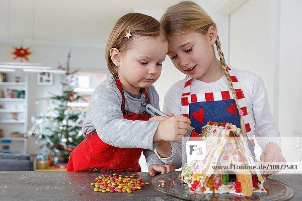 Mädchen an der Küchentheke schmücken gemeinsam das Lebkuchenhaus