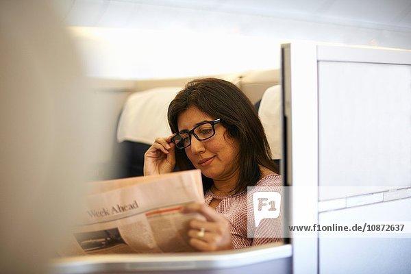 Reife Geschäftsfrau liest Zeitung im Flugzeugsitz