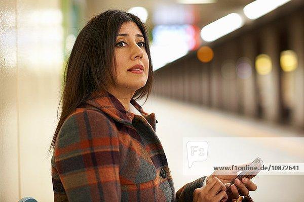 Reife Geschäftsfrau an städtischer U-Bahn-Station mit Smartphone  Tokio  Japan