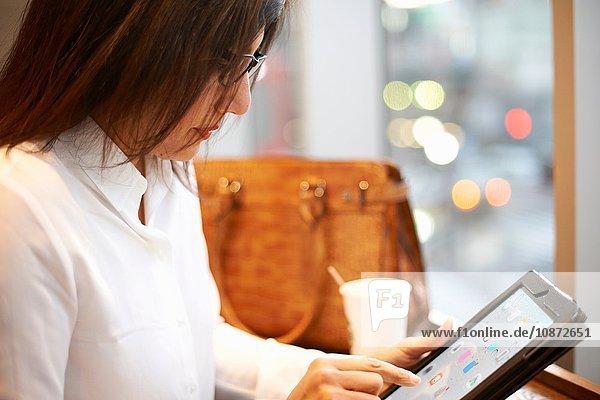 Mature businesswoman using digital tablet at city cafe  Tokyo  Japan